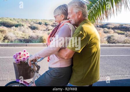 Beau et joli couple de modèles adultes jouant sur le même bike outdoor. activité de loisirs pour les professionnels retraités en vacances en place tropicales près de l'océan. Ténérife locations de concept et smiling people with palm tree Banque D'Images