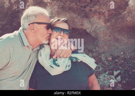 Heureux couple en vacances à Tenerife avec des cheveux blancs et lunettes de sourire et s'embrassent sur la joue Banque D'Images