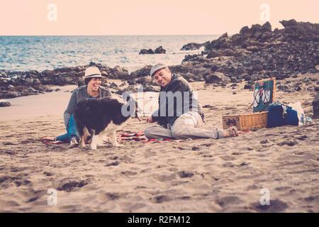Beau Beau couple d'hommes et de femmes font un pic nic sur la plage près de thw vague avec un chien border collie. L'amour et l'amitié concept dans les vacances d'été à Tenerife. couleurs rétro vintage et pittoresque place Banque D'Images