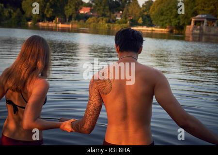 Jeune couple d'entrer dans un lac, baignade Banque D'Images