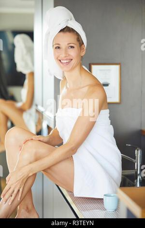 Portrait of smiling woman wrapped in , assis sur le lavabo dans la cuisine Banque D'Images