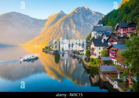 Vue de carte postale classique de la célèbre ville au bord du lac de Hallstatt dans les Alpes avec des passagers à bord d'un navire traditionnel au début de lumière du matin au lever du soleil sur une belle d Banque D'Images