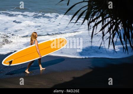 Fille sportive en bikini avec planche de surf à pied sur la plage de sable noir. Jeune femme surfeur géré par eau douce avec mousse blanche. Les personnes actives aventure sports Banque D'Images