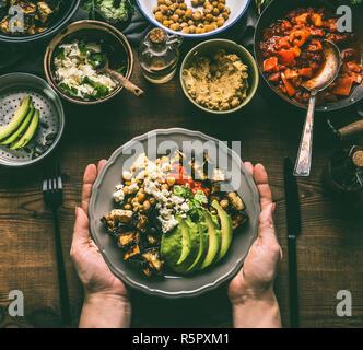 Les mains tenant avec bol végétarien sain avec divers légumes grillés, d'avocat et de pois chiches hoummos sur fond rustique, vue du dessus. Nettoyer Banque D'Images