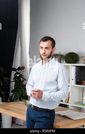 Office de thème d'affaires. Handsome young man confiant et solide, avec une barbe, debout dans cette chambre lumineuse sur le lieu de travail. habillé élégamment shirt Banque D'Images