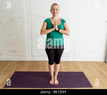 Portrait of young smiling attractive professeur yogi woman standing in namaste prier de poser dans les cool urban style studio de remise en forme d'entraînement en Banque D'Images