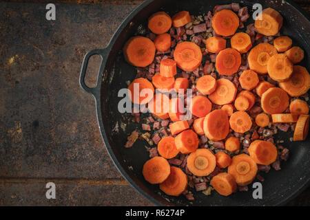 Les carottes et le lard dans la poêle sur le fond métallique Banque D'Images