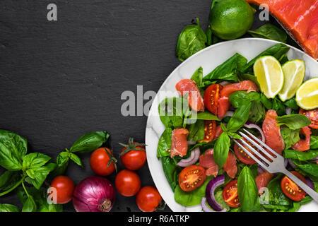 Salade fraîche au saumon, épinards, tomates cerises, l'oignon rouge et le basilic dans la plaque de marbre avec une fourchette sur fond d'ardoise noire. Une alimentation saine à concept. Banque D'Images