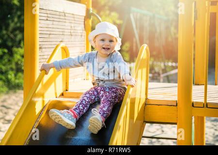 Happy smiling enfant le curseur en aire de jeux en plein air Banque D'Images