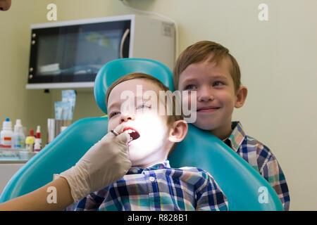 Réception à l'art dentaire. Un petit garçon est sur la table et son frère reste derrière Banque D'Images