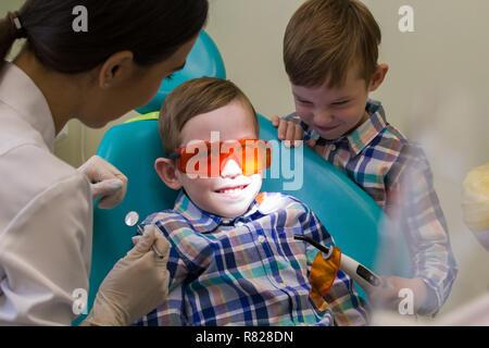 Réception à l'art dentaire. A smiling little boy jette sur la table Banque D'Images