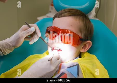 Réception à l'art dentaire. Un petit garçon est sur la table et de prendre un traitement Banque D'Images