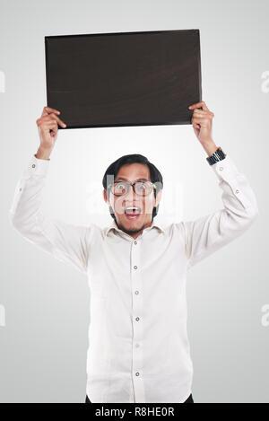 Photo image portrait de funny businessman ou enseignant ou étudiant montrant surpris avec tableau noir vide visage souriant, holding blackboard sur hi Banque D'Images