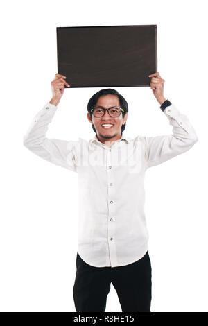 Photo image portrait de funny businessman ou enseignant ou étudiant montrant avec tableau noir vide visage souriant, holding tableau noir sur sa tête, vo Banque D'Images