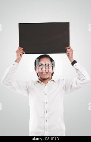 Photo image portrait de funny businessman ou enseignant ou étudiant montrant avec tableau noir vide visage souriant, holding tableau noir sur sa tête Banque D'Images