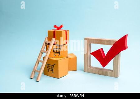 Une boîte-cadeau sur une pile de boîtes et une marque rouge. Le concept de trouver le cadeau idéal. Liste d'achat. Vente, gros rabais et d'excitation avant Banque D'Images