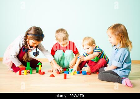 Les enfants jouent avec des blocs en bois à l'école maternelle Banque D'Images