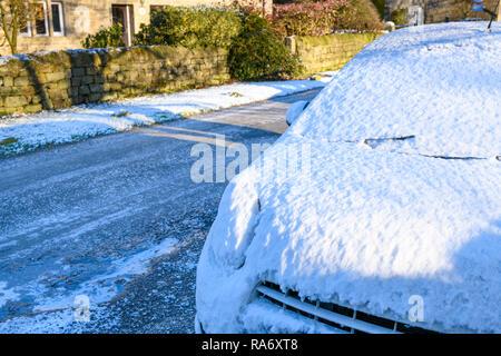 Close-up of voiture garée sur la rue main glacée de petit village rural sur la neige glaciale journée d'hiver - Timble, North Yorkshire, England, UK Banque D'Images