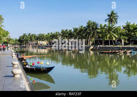 Les petits bateaux traditionnels sur la rivière Thu Bon et bordée de palmiers dans le vieux quartier de la ville historique. Hoi An, Quang Nam, Vietnam, Asie Banque D'Images