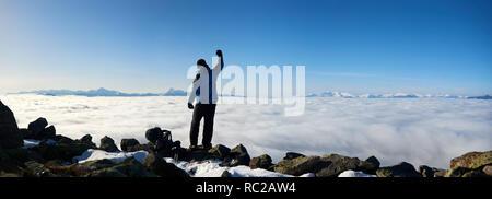 Vue arrière de l'randonneur homme avec bras soulevé debout sur rocky hill sur copie espace fond de vallée brumeuse magnifique rempli de nuages blancs, sno Banque D'Images