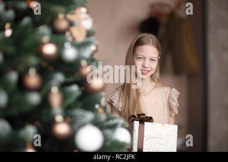 Happy girl with Christmas Gift, debout près de l'arbre de Noël Banque D'Images