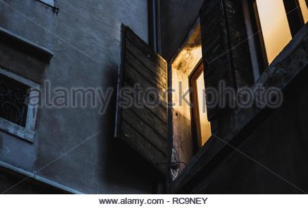 Vue depuis la rue d'une chaude lumière fenêtre à Venise, Italie Banque D'Images