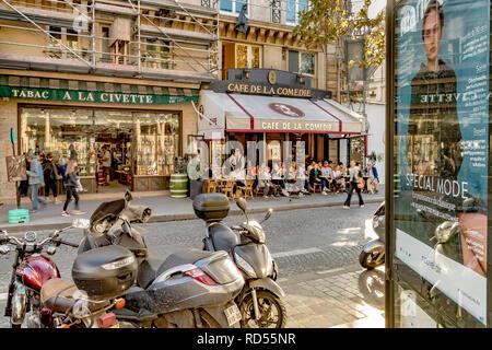 Des scooters garés dans une rue de Paris à côté d'un panneau publicitaire avec les gens assis dehors en train de déjeuner au café de la Comédie, rue Saint Honoré, Paris Banque D'Images