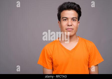 Portrait de jeune homme contre l'arrière-plan gris Banque D'Images