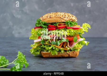 Big sandwich au jambon, fromage et légumes frais sur une carte. Le petit-déjeuner gratuit. Banque D'Images