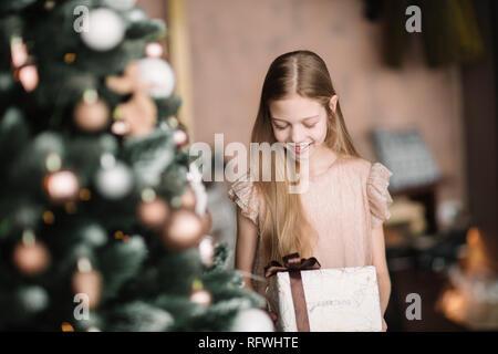 Fille avec une boîte-cadeau, debout près de l'arbre de Noël . Banque D'Images