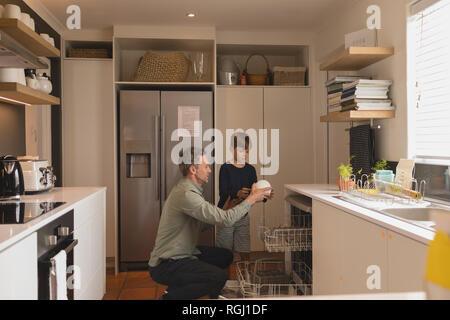 Père et fils l'organisation de la vaisselle sale dans le lave-vaisselle Banque D'Images