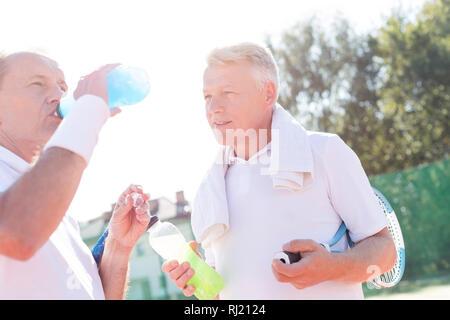 Homme mature à la recherche de la bouteille de boisson ami senior en se tenant sur le court de tennis durant l'été Banque D'Images