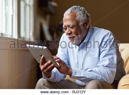 Man s'amusant à l'aide d'une tablette numérique. Banque D'Images