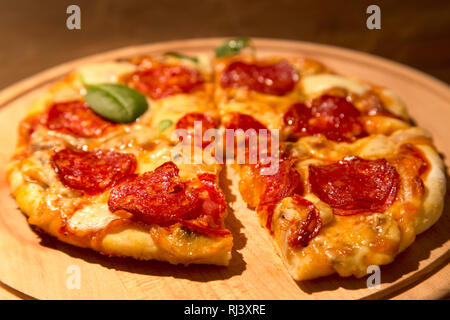 Pizza au pepperoni, sur une plaque de bois Banque D'Images