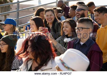 Heureux Latinx fans prenant en selfies à gradins d'un match de baseball Banque D'Images
