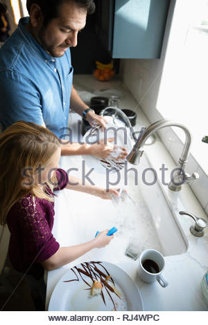 Père et fille Latinx lave-vaisselle à l'évier de cuisine Banque D'Images