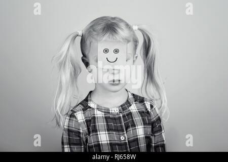 Portrait noir et blanc de triste malheureux Caucasian preschool girl avec drôle sticky note sur son visage. Kid: exprimer des sentiments. Concept de diffic Banque D'Images