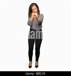 Belle femme d'affaires d'âge moyen prêt à combattre avec fist, geste de défense en colère et contrarié face, peur de problème Banque D'Images
