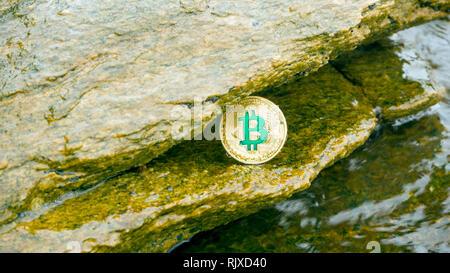 La pièce d'or de Bitcoin se trouve dans la roche avec des vagues de la mer. Bitcoin est une façon moderne d'échange cette crypto-monnaie est un moyen pratique de paiement i Banque D'Images