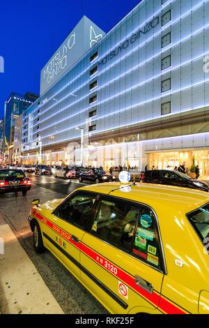 Tokyo Ginza, l'heure bleue. Taxi jaune en premier plan avec l'énorme magasin Matsuya illuminé de l'autre côté de la rue. La nuit. Banque D'Images