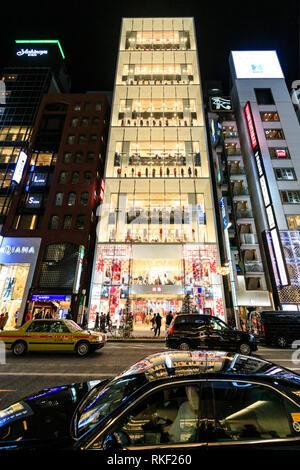 Ginza de Tokyo, la nuit. Dans Street View de Flagship Uniqlo à la façade de verre 12 magasin histoire allumé. Taxi en premier plan. Les arbres de Noël sur le trottoir. Banque D'Images