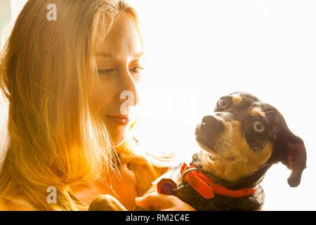 Young woman smiling comme elle tient son chien. Banque D'Images