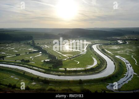 Ingelmunster, East Sussex, UK. Feb 13, 2019. Le soleil s'élève au-dessus de la rivière Cuckmere qui serpente à travers le Parc National des South Downs. Crédit: Peter Cripps/Alamy Live News Banque D'Images