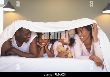 Happy African American family sous couverture et à chaque autre Banque D'Images