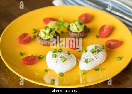 Œufs pochés avec avocat farci aux champignons, tomates, oignons verts et sur une plaque jaune sur une table en bois Banque D'Images