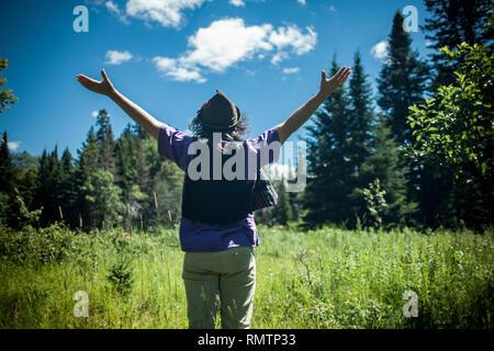 Homme portant un chapeau avec ses bras en profitant d'une belle journée ensoleillée dans la nature, vu de derrière Banque D'Images