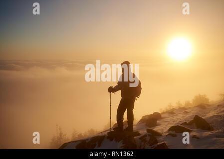 Vue arrière de l'randonneur avec sac à dos et des bâtons de randonnée reposant sur rocky mountain peak sur copie espace fond de vallée brumeuse magnifique rempli de puffy blanc nuages à l'aube à l'hiver. Banque D'Images