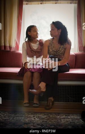 Fille assise à côté de sa mère à un siège côté fenêtre. Banque D'Images