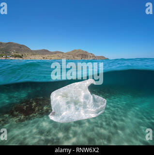 Sous-marins de la pollution d'un sac de plastique à la dérive en Méditerranée avec la côte en arrière-plan, vue fractionnée de la moitié au-dessus et au-dessous de la surface de l'eau, Espagne Banque D'Images