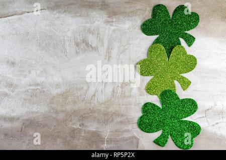 Trois trèfles vert dans une ligne vertical sur le côté droit. L'abondance de l'espace de copie. Banque D'Images